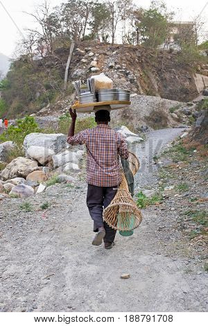 LAXMAN JHULA, INDIA - APRIL 20, 2017: Seller with his goods on his way home in Laxman Jhula on the 20th april 2017 in India