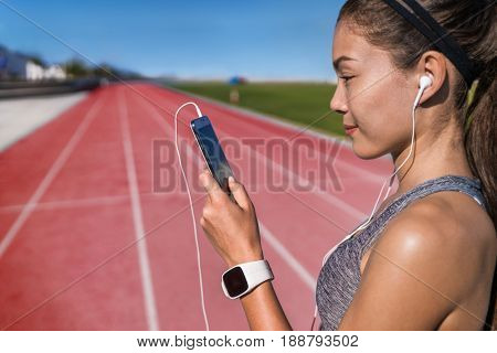 Runner listening to smart phone music app on red running tracks. Asian woman athlete with earphones and smartphone ready to do run cardio workout at track and field stadium. Jogging motivation.