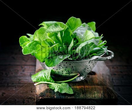 Spinach. Fresh organic spinach leaves in metal colander on a wooden table. Diet, dieting concept. Vegan food, healthy eating. Dark rustic style photo.