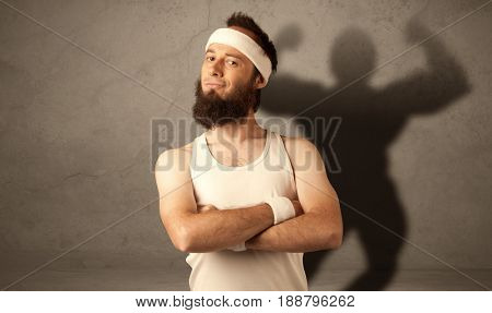 A funny young guy posing in front of brown background with musculous body shadow reflected on the wall
