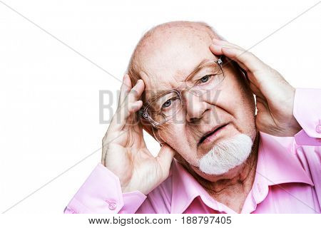 The old man keeps a hand on his head. Headache, blood pressure. Health care for the elderly people.