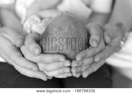 Family of three together, parents holding head of their first child, gray photo