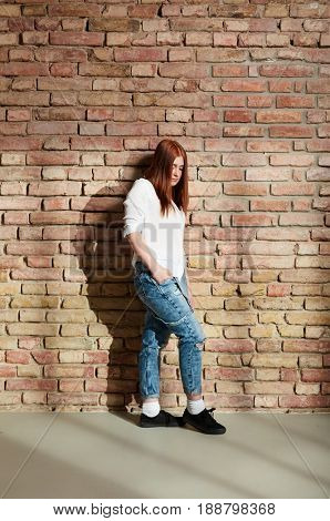 Young woman in jeans leaning against brick wall, thinking.