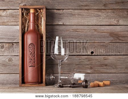 Wine bottle in box and wine glasses in front of wooden wall. With copy space