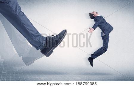 Businessman big foot kicking small, young businessman who is flying