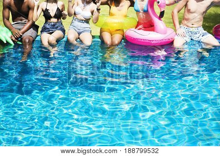 Group of diverse friends enjoying summer time by the pool with inflatable tubes
