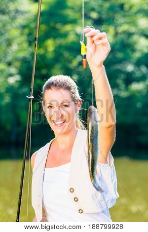 Sport fisherwoman showing her catch dangling from the fishing rod
