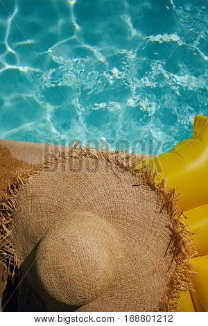 hat on a yellow air mattress near swimming pool. Tropical summer concept.