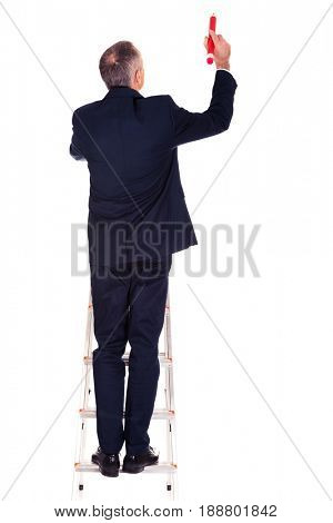 Businessman climbing ladder with oversized pencil