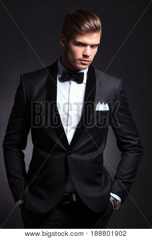 elegant young fashion man in tuxedo holding his hands in his pockets and looking at you questioningly.on black background