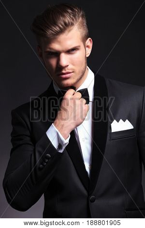 elegant young fashion man in tuxedo fixing his bow tie while looking at the camera .on black background