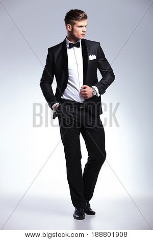 full length picture of an elegant young fashion man in tuxedo holding his hand om his jacket while looking away. on gray background