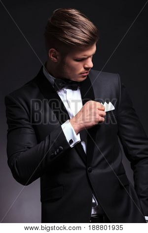 elegant young fashion man in tuxedo adjusting his chest pocket handkerchief while looking at it. on black background