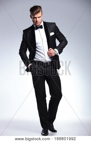 full length photo of an elegant young fashion man in tuxedo holding a hand on his unbuttoned jacket and one in his pocket while looking at camera. on gray background