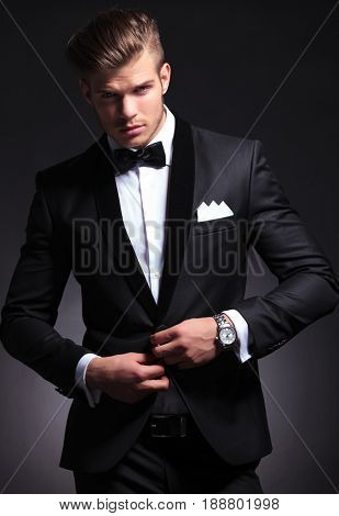 elegant young fashion man in tuxedo unbuttoning his jacket while looking at the camera.on black background