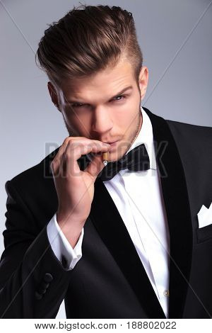 closeup portrait of an elegant young fashion man in tuxedo looking at the camera while taking a smoke from his cigar. on gray background