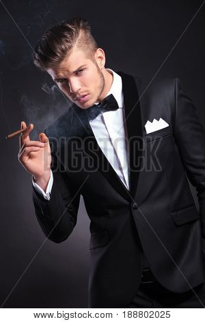 angle view of an elegant young fashion man in tuxedo smoking while holding a hand in his pocket and smiling. on black background