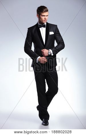 full length photo of an elegant young fashion man in a tuxedo looking at the camera while adjusting his jacket. on gray background