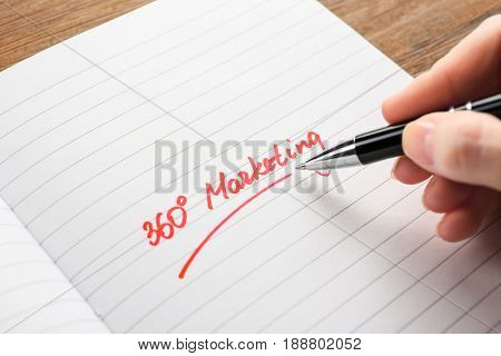 Woman writing text 360 MARKETING in open notebook, closeup