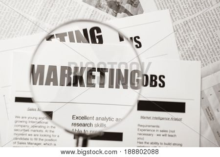Paper sheet with word MARKETING through magnifier, closeup
