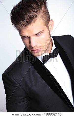 closup angle view of an elegant young fashion man in tuxedo looking away from the camera. on gray background