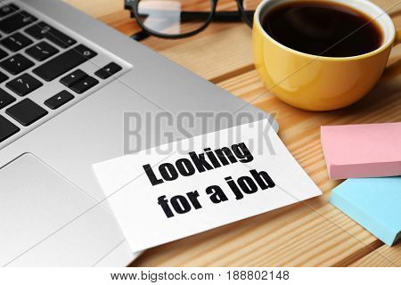 Paper sheet with text LOOKING FOR A JOB and laptop on table