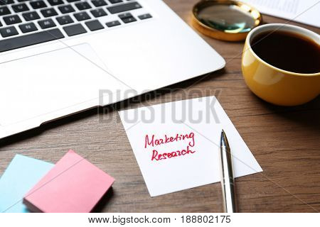 Paper sheet with text MARKETING RESEARCH and laptop on table