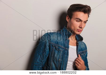 sad man in jeans jacket looks down on grey background