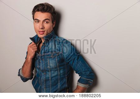 fashion man in jeans jacket looks to side at copyspace on grey wall