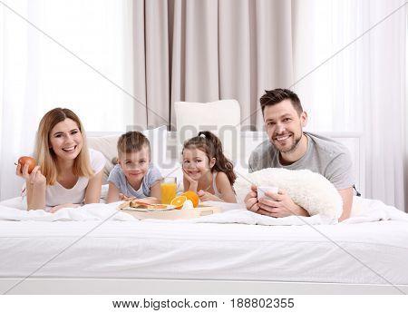 Happy smiling family having breakfast in bed