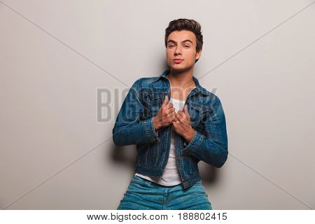 young man pulling his jeans jacket's collar and looks at the camera on grey wall