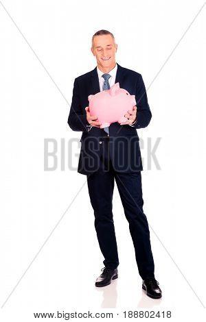 Cheerful businessman holding piggybank