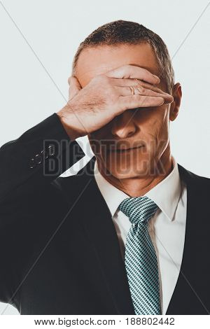 Portrait of stressed businessman covering his face