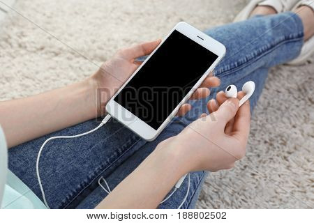 Woman with modern phone and earphones sitting on floor. Concept of audiobook