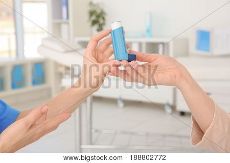 Doctor giving adult woman inhaler in clinic