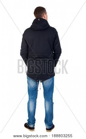 Back view of handsome man in winter jacket  looking up.   Standing young guy in parka. Rear view people collection.  backside view of person Man in warm jacket with his hands in his pockets costs.