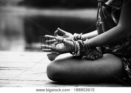 woman in a meditative yoga position sit on wooden pontoon on the lake wearing lot of bracelets and rings lower body in black and white