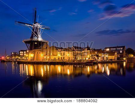 View of Harlem landmark  windmill De Adriaan on Spaarne river in the night illuminated. Harlem,  Netherlands