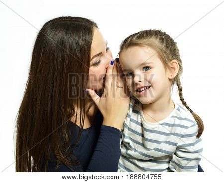 Women's secrets. Mom tells secret to her daughter. Family portrait. Happy mother with her cute little daughter posing at studio over white background.
