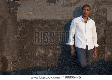 Black man leaning on wall