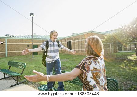 Caucasian mother greeting son