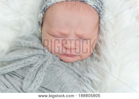 Sleeping frowning baby with gray knitted hat on, wrapped in gray blanket on pillow, topview