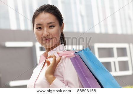 Chinese businesswoman carrying shopping bags