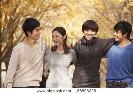 Chinese friends hugging outdoors