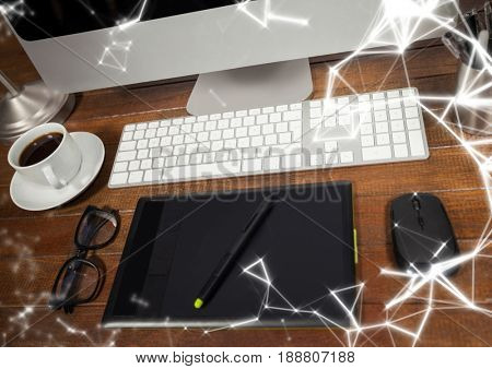Digital composite of Graphics tablet in front of computer with white network overlay