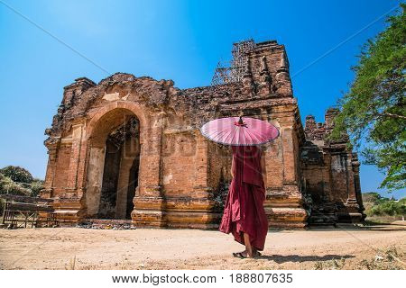 Buddhist with umbrella in front of  Pahto Thamya Temple, Old Bagan, Myanmar.(Burma)