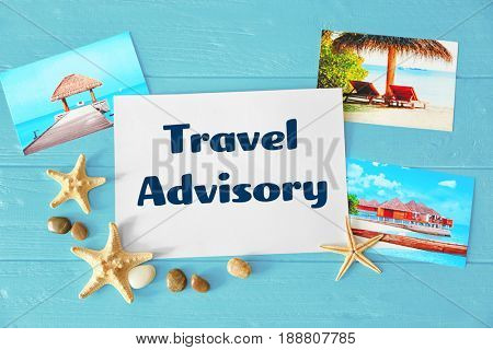 Concept of tourism. Paper with text TRAVEL ADVISORY and photos on wooden background
