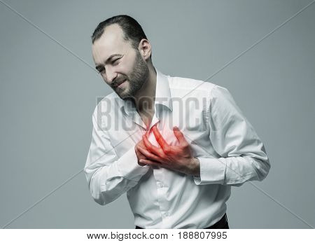 Heart attack concept. Man suffering from chest pain on gray background