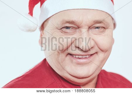 Close up portrait of smiling aged man wearing Santa Claus hat and red shirt against white background - Christmas concept