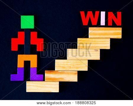 Concept of building success foundation. wooden block in the shape of human step on stacked wooden block like stairs to WIN. Business development and growth concept.